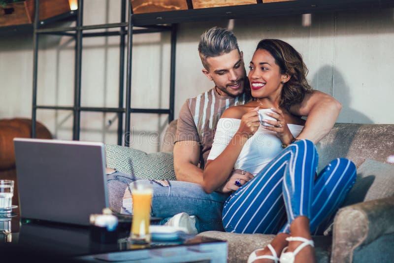 花费在咖啡馆的年轻人种间夫妇时间 免版税图库摄影