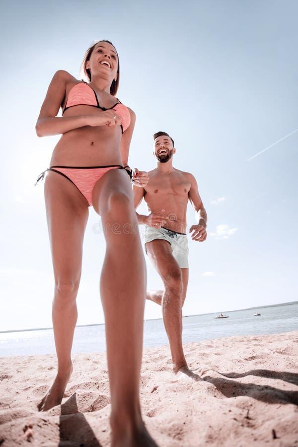 花费无忧无虑的时间的愉快的夫妇在海滩上户外 免版税库存照片