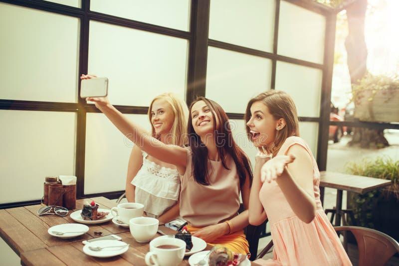 花费时间一起喝在咖啡馆的三个女朋友咖啡,食用早餐和点心 免版税库存照片