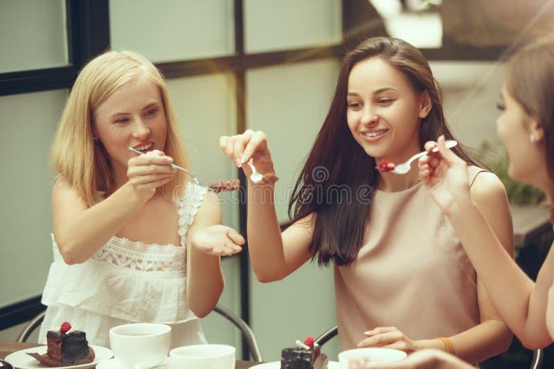 花费时间一起喝在咖啡馆的两个女朋友咖啡,食用早餐和点心 免版税库存图片