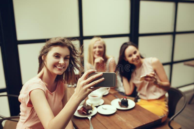 花费时间一起喝在咖啡馆的两个女朋友咖啡,食用早餐和点心 免版税图库摄影