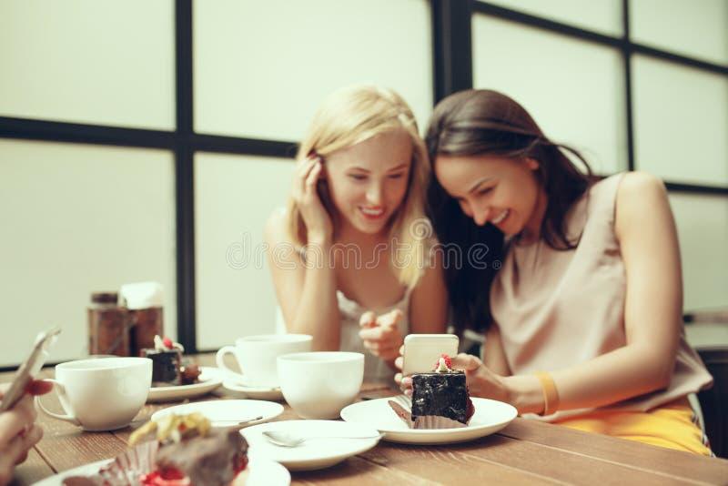 花费时间一起喝在咖啡馆的两个女朋友咖啡,食用早餐和点心 库存图片