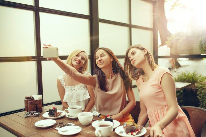 花费时间一起喝在咖啡馆的两个女朋友咖啡,食用早餐和点心 免版税库存照片