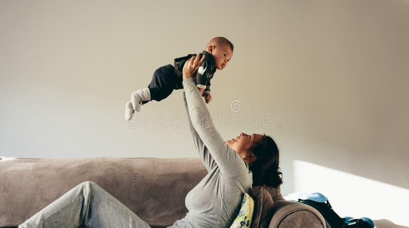 花费时间的妇女使用与她的婴孩 免版税图库摄影