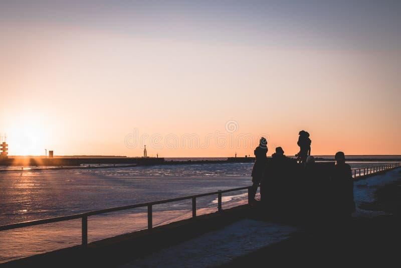 花费时间的家庭在日落期间由海 免版税图库摄影