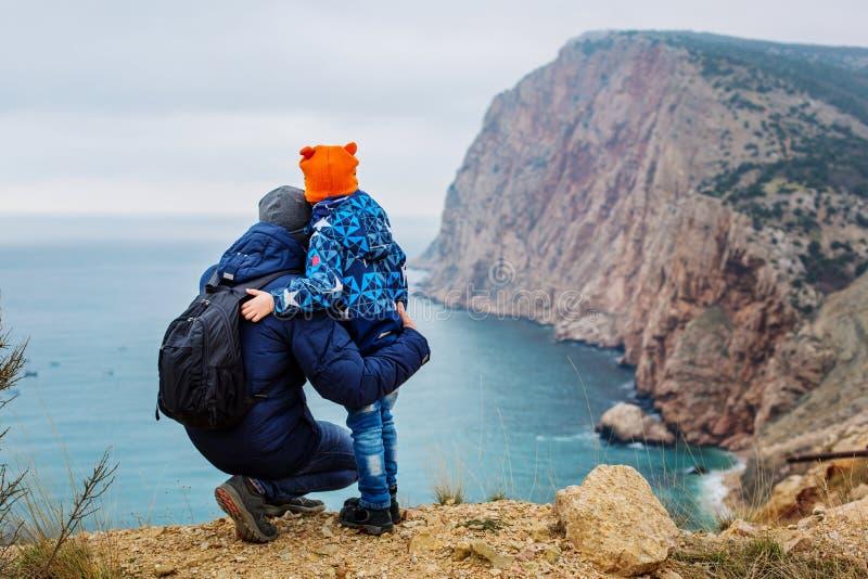 花费时间的父亲和儿子与美丽的山和海一起 免版税库存照片