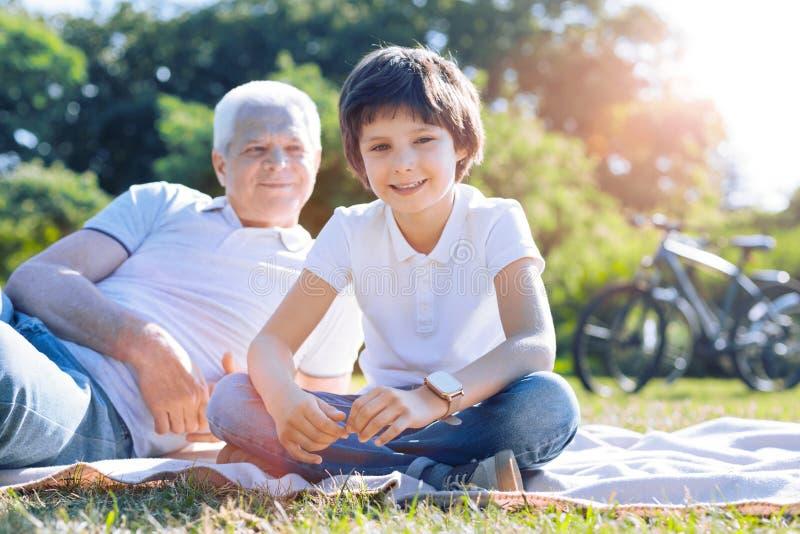 花费时间的轻松的孩子户外与祖父 库存图片