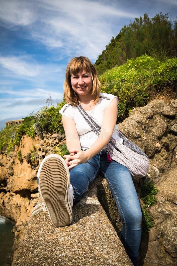 花费美妙的时间的愉快的年轻红发妇女在大西洋海岸线放松在风景海景的,比亚利兹,巴斯克地区上, 免版税库存图片