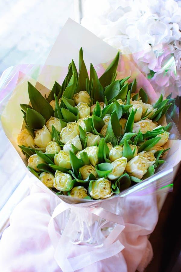 花郁金香在一条腿的在婚姻庆祝的商店的餐馆内部floristry或 免版税库存图片