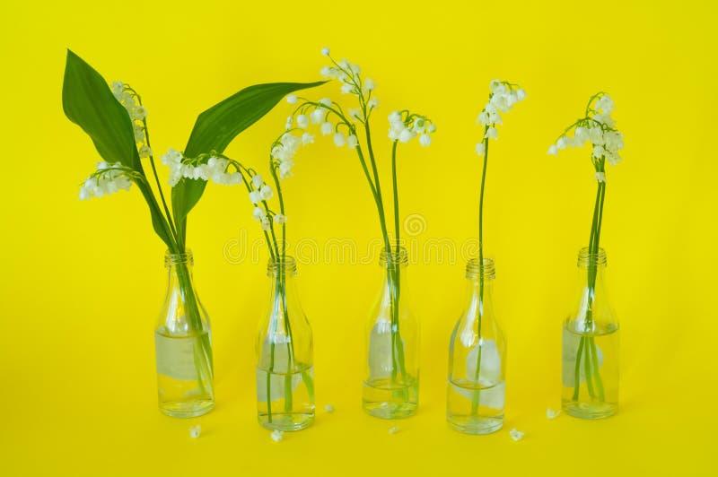 花铃兰美丽的花束在小的玻璃瓶的在明亮的黄色背景,白天,拷贝空间, n 免版税库存照片