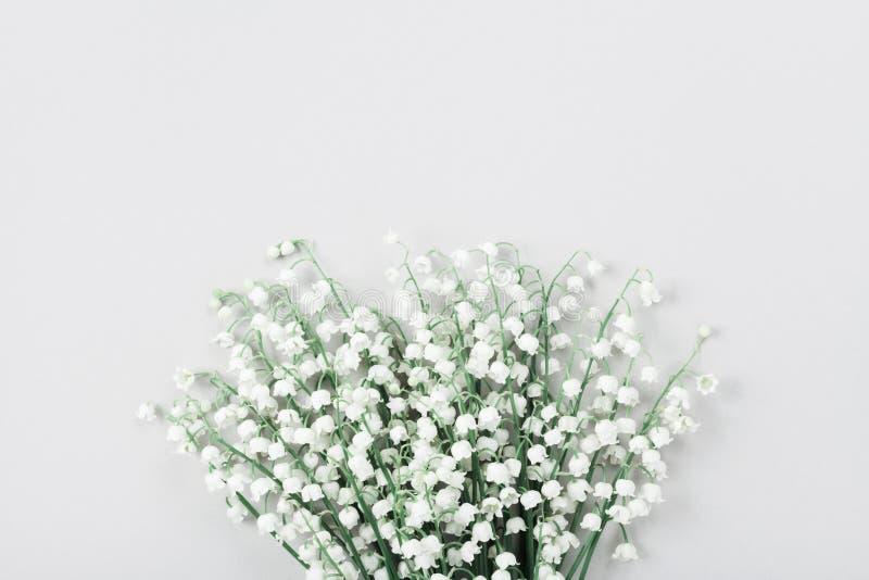 花铃兰美丽的花束在淡色桌上的从上面 最小的构成和平的位置样式 免版税库存图片