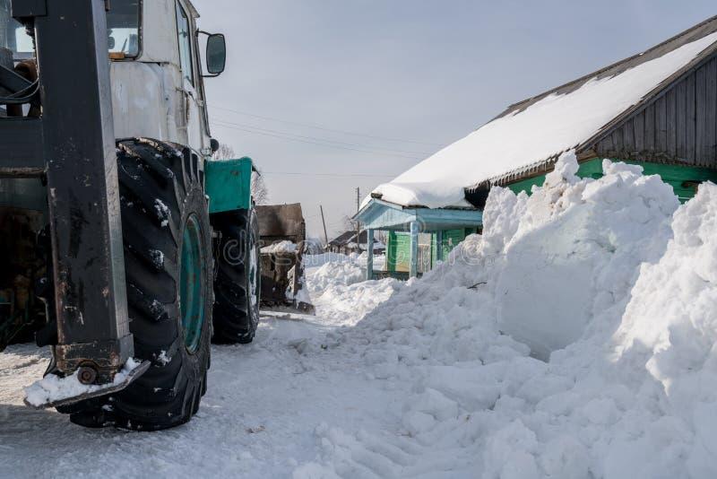 花雪时间冬天 拖拉机在村庄清洗雪 图库摄影