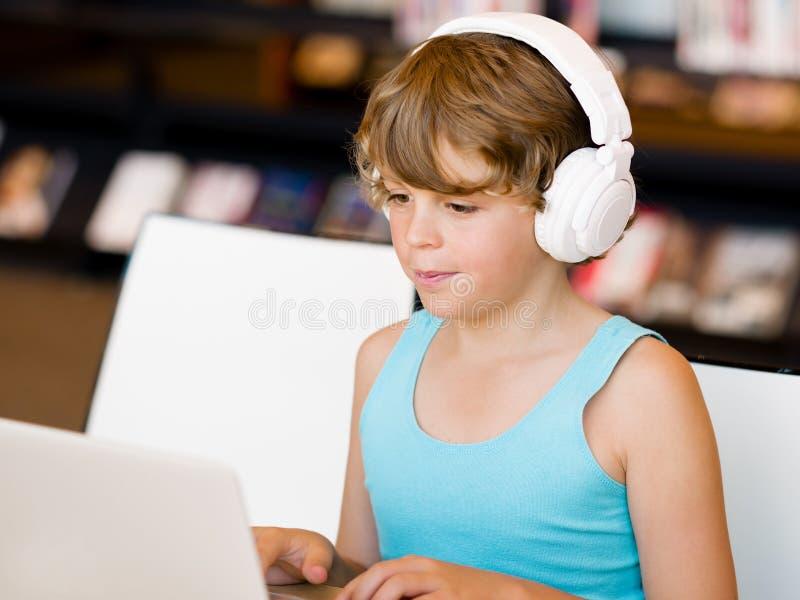 花费与笔记本的男孩时间 免版税库存图片