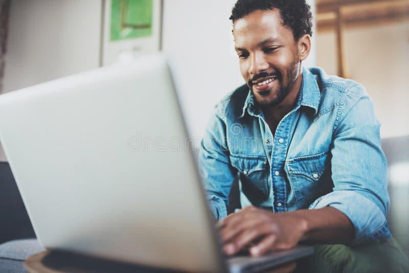 花费在沙发和使用的微笑的有胡子的非洲人膝上型计算机的业余时间在现代家 青年人享用的概念 库存图片