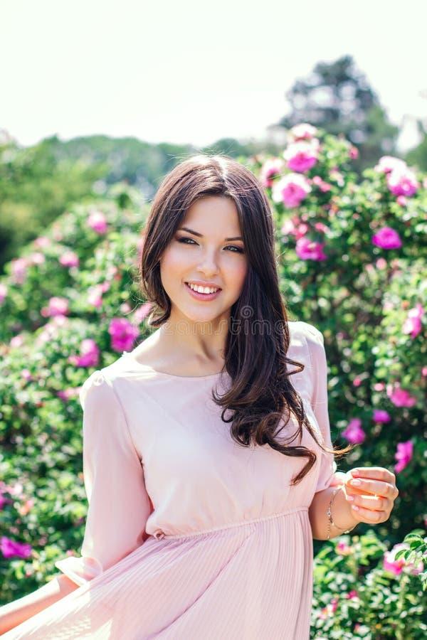 花围拢的美丽的年轻愉快的微笑的妇女室外时尚照片  杜娟花开花浅关闭dof的花出现 免版税库存图片