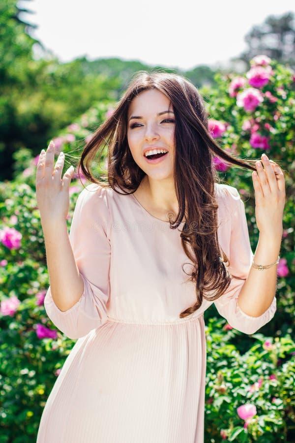 花围拢的美丽的年轻愉快的微笑的妇女室外时尚照片  杜娟花开花浅关闭dof的花出现 免版税库存照片