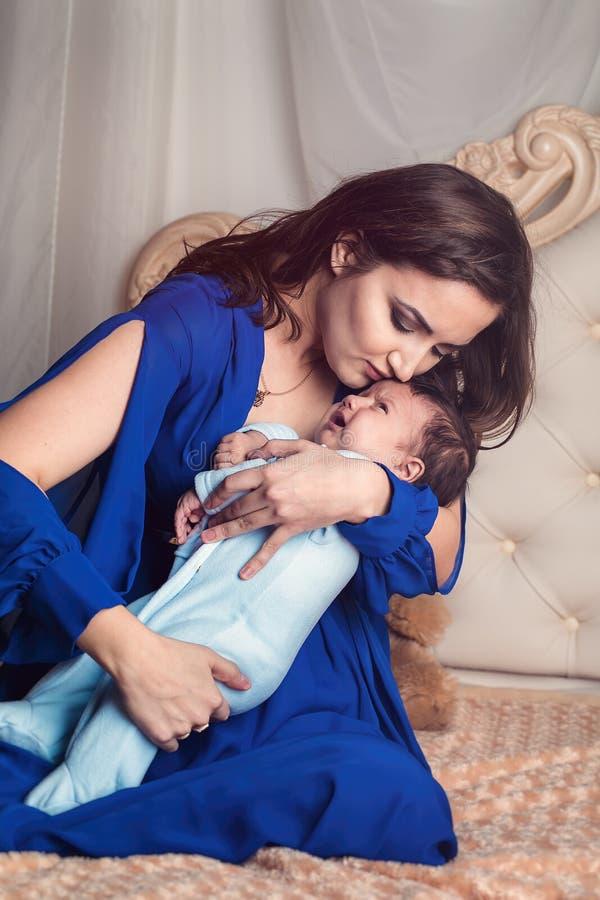 花费时间和亲吻她的年轻母亲3个月大婴孩 免版税库存照片