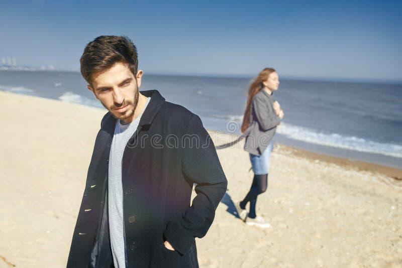 花费时间的愉快的年轻夫妇在海岸上在春天 库存照片