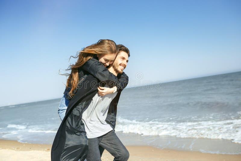 花费时间的愉快的年轻夫妇在海岸上在春天 库存图片