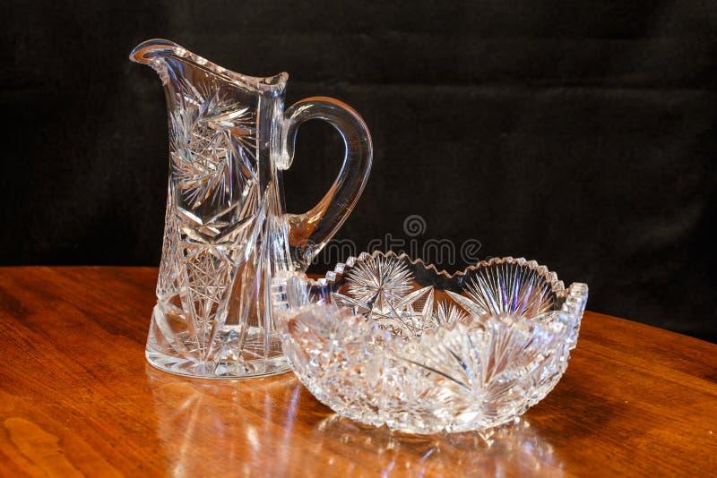 刻花玻璃水晶碗和投手在木表上 免版税库存图片
