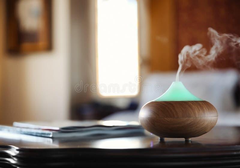 芳香在木桌上的油分散器 免版税库存图片