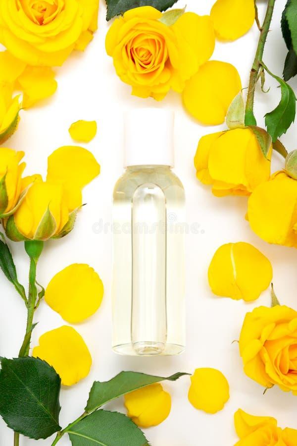 芳香植物的化妆用品 Skincare家与黄色瓣的温泉治疗,上升了开花,瓶精油,奉承话 免版税库存图片
