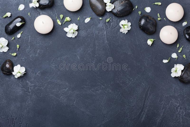 芳香疗法和温泉构成装饰了在黑石背景顶视图的花 秀丽治疗和放松概念 免版税库存图片
