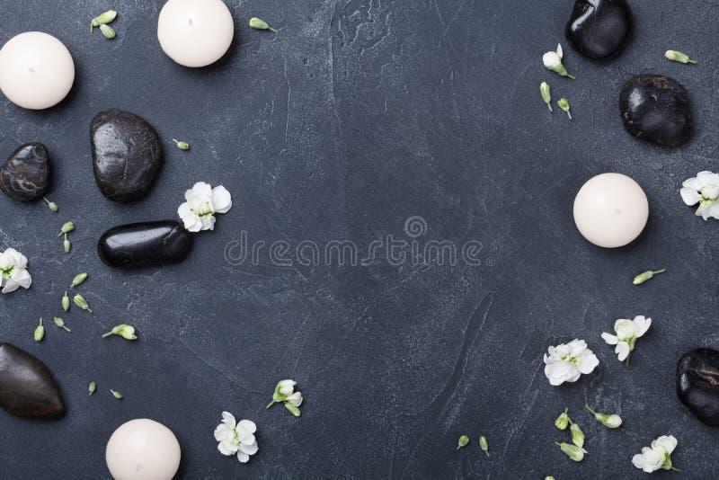 芳香疗法或温泉的构成装饰了在黑石背景顶视图的花 秀丽治疗和放松概念 库存照片