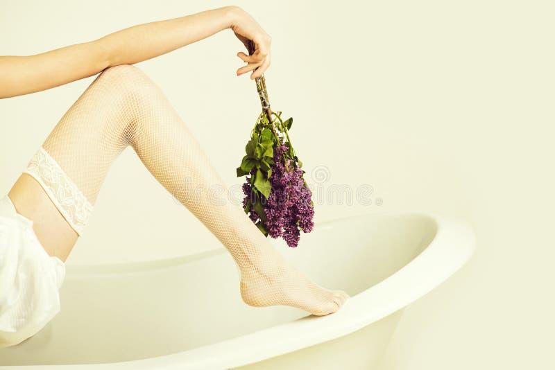 芳香疗法,温泉 方式内衣 淡紫色花、腿在渔网长袜和手有束的 免版税图库摄影