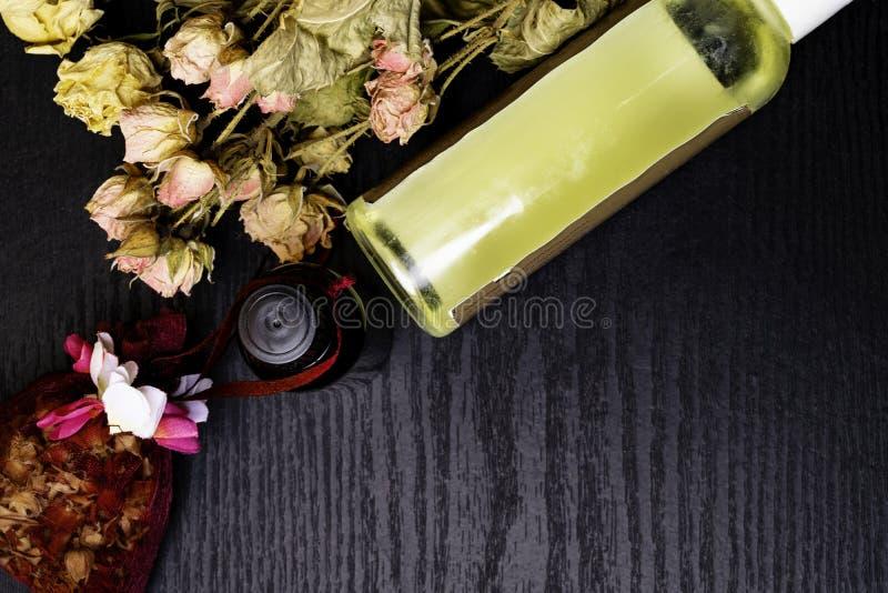 芳香疗法-两瓶与干燥玫瑰花瓣的精油 库存照片