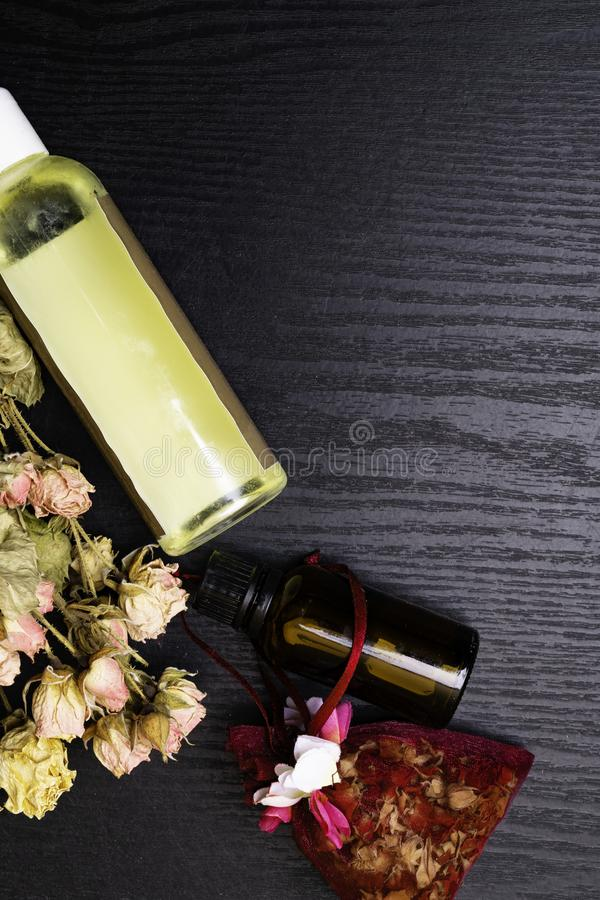 芳香疗法-两瓶与干燥玫瑰花瓣的精油 免版税库存照片