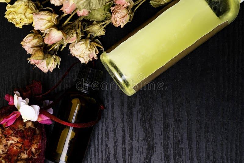 芳香疗法-两瓶与干燥玫瑰花瓣的精油 免版税图库摄影