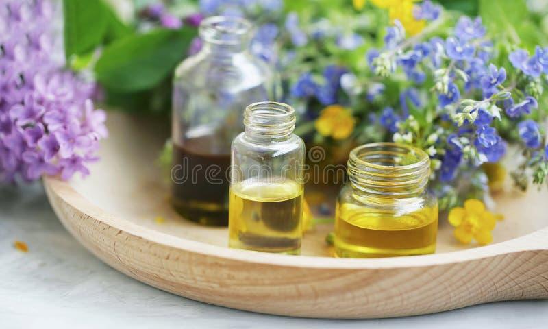 芳香疗法 自然药用植物和草本油瓶、自然花卉萃取物和油,自然油 免版税库存照片