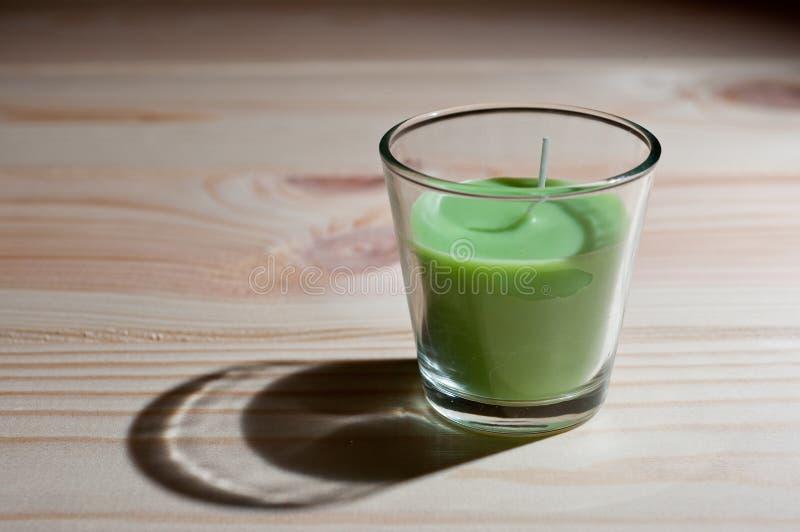 芳香蜡烛是绿色的与茶树的气味在黑暗的背景的 库存照片