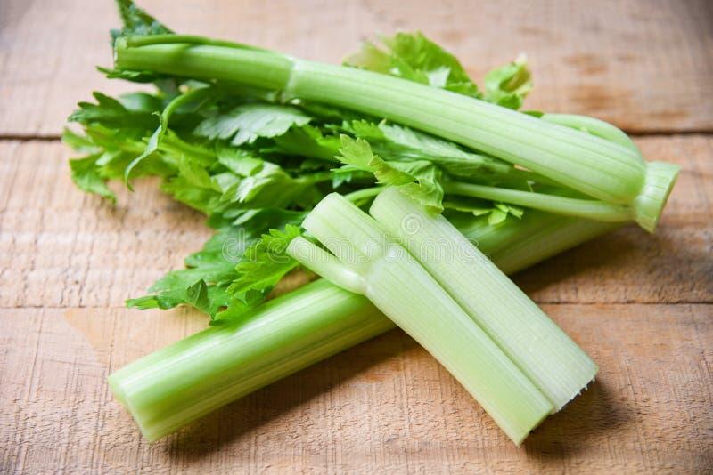 芹菜杆和叶子新鲜蔬菜-束在木背景的芹菜茎 免版税库存图片