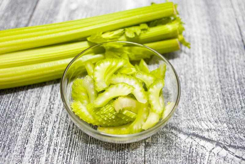 芹菜茎,切了在玻璃碗的芹菜在木背景 图库摄影