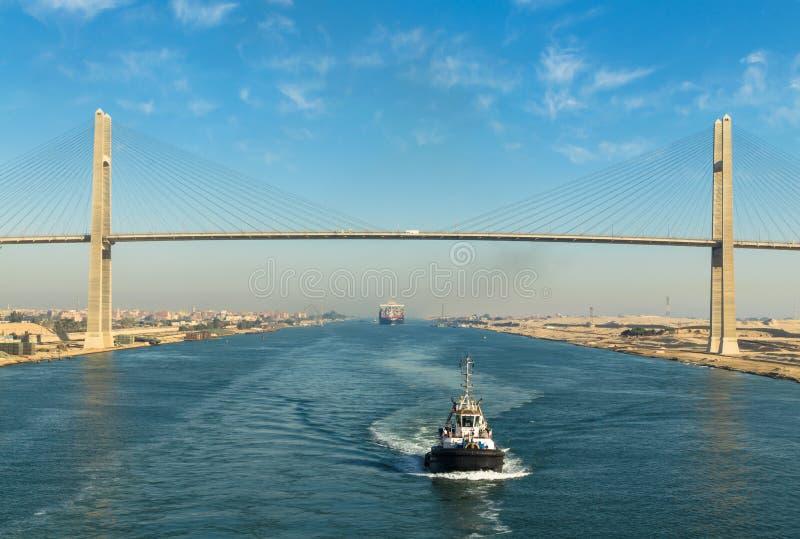 苏伊士运河,埃及, 2017年:运输穿过苏伊士运河的` s护卫舰,在背景-苏伊士运河桥梁中 免版税库存照片