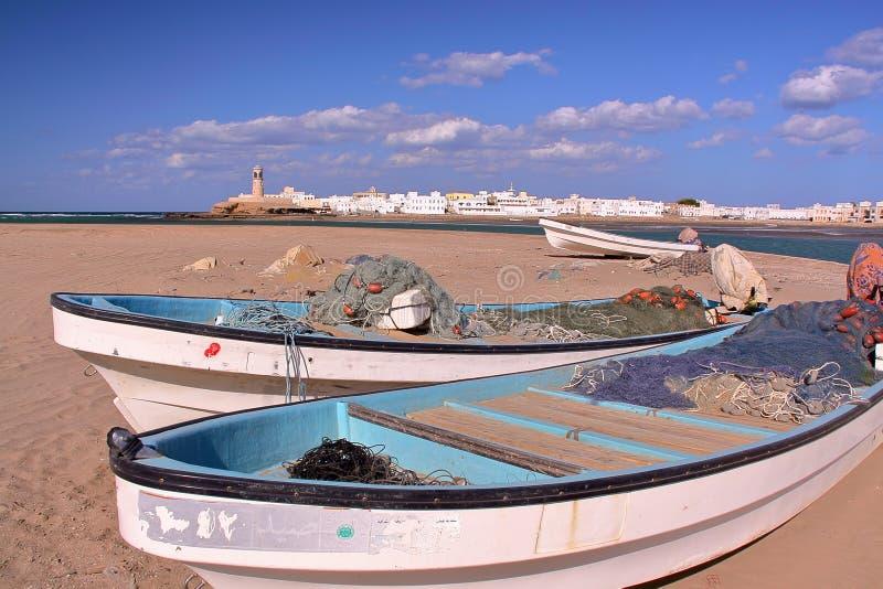 苏尔,阿曼:Ayjah看法与渔船的在前景 库存照片