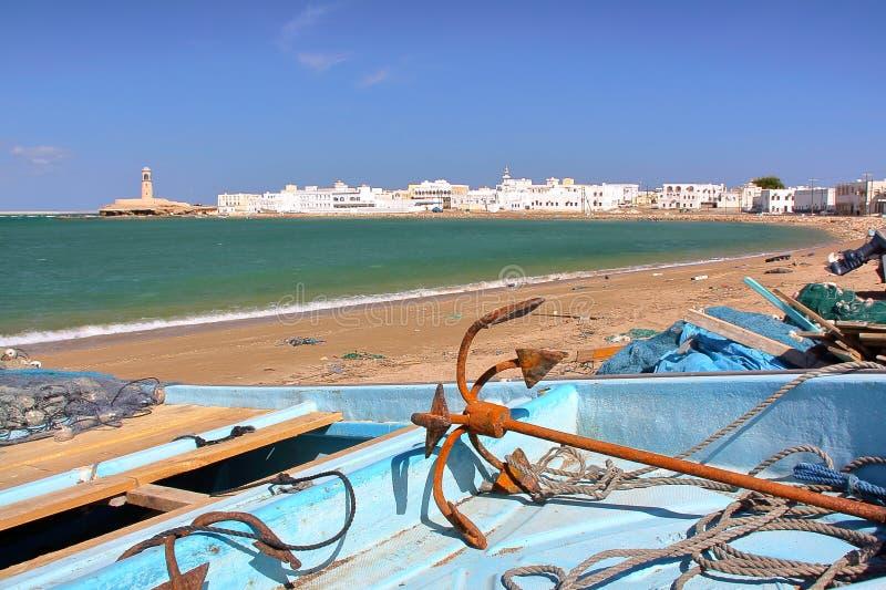 苏尔,阿曼:Ayjah看法从海滩的与在前景的一个渔船 免版税库存图片