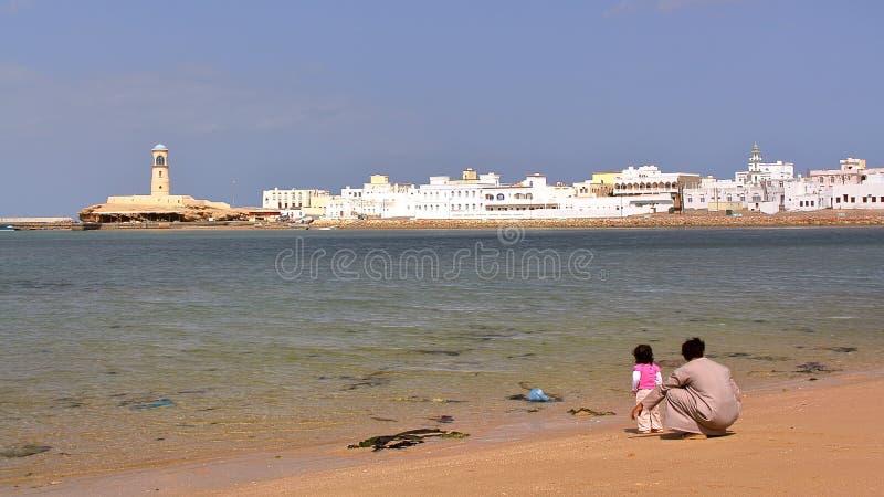 苏尔,阿曼- 2012年2月6日:Ayjah看法从海滩的与一个阿曼人和他的小女儿前景的 免版税库存照片