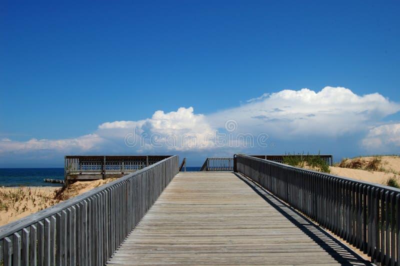 苏必利尔湖畔的木甲板有一蓝色的backgorund的白色云彩 库存图片