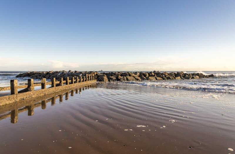 苏格兰一个阳光明媚的日子,在阿伯丁市的海滩建有一座风景优美的防波堤 免版税库存图片