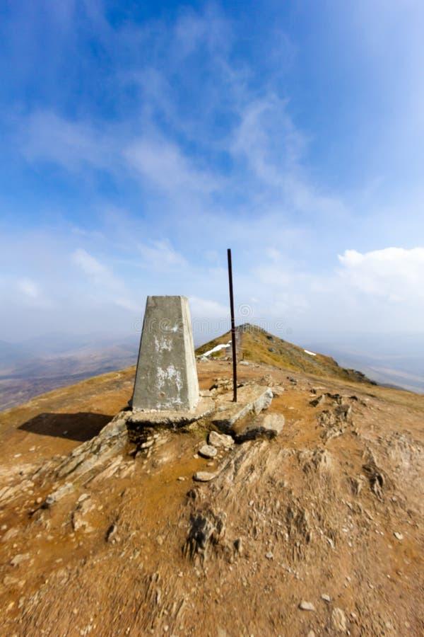 苏格兰山有被腐蚀的岩石土壤的本Vorlich的山顶trig点的看法在庄严天空蔚蓝和高度下 库存照片