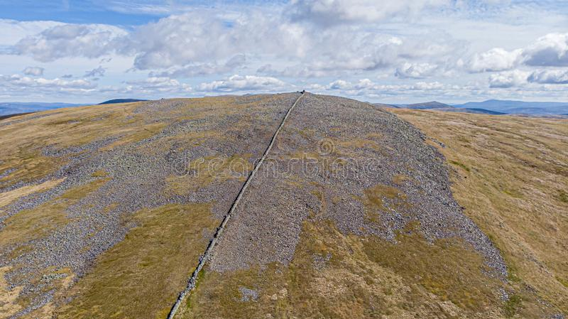 苏格兰岩石曼诺山顶和在一朵庄严天空蔚蓝和白色云彩下的石墙的一张鸟瞰图与岩石倾斜的 免版税库存照片