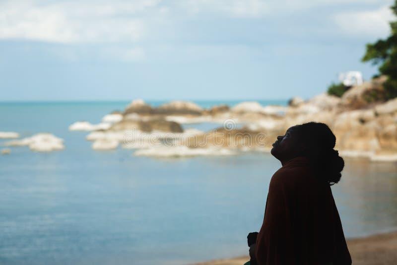 苏梅岛海岛,泰国,2018年7月 年轻非裔美国人的妇女身分黑暗的剪影在海和岩石的背景的 免版税库存照片