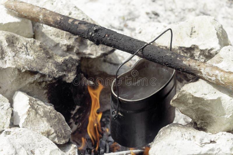 苏联水垂悬在棍子的军队罐在火 库存照片