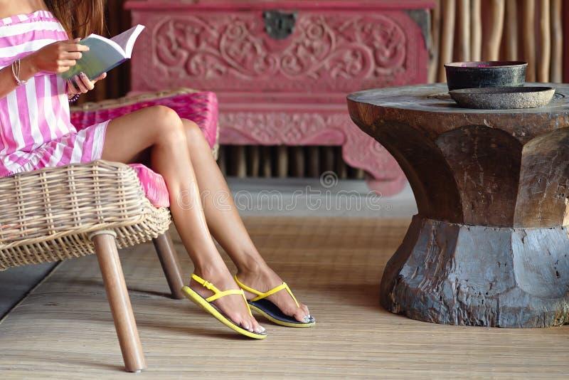 苗条坐一个桃红色沙发和读书的结算美女 r ?? 图库摄影