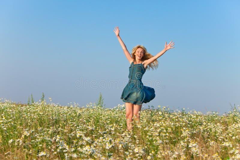 年轻苗条妇女的画象的蓝色牛仔裤的sundress在camomiles领域在一个晴天 免版税库存图片