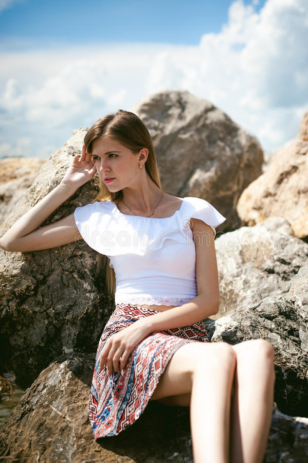 苗条少妇画象石头的在海附近 库存照片