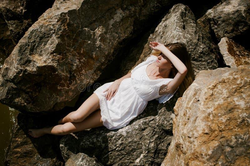 苗条少妇画象石头的在海附近 免版税库存照片